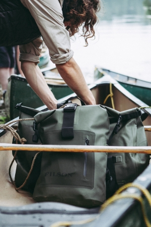 Loading Filson dry bags into a canoe