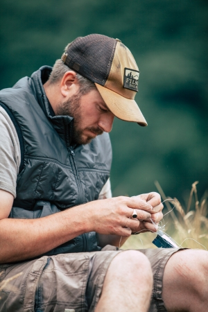 Fly tying in a Filson ultralight vest and trucker cap