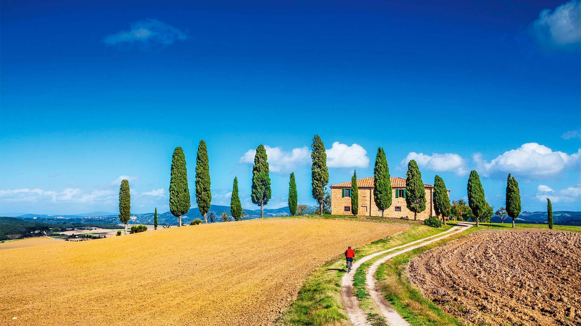 Classic panorama view of scenic Tuscany landscape with farmhouse and male cyclist on a country road on a beautiful sunny day in summer, Italy