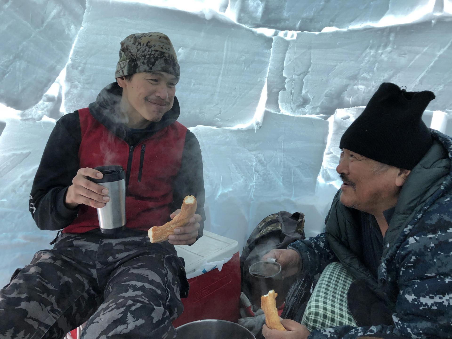 Qalingo Sivurapak and Inukpak Itukallak enjoy bannock in an igloo in Nunavik