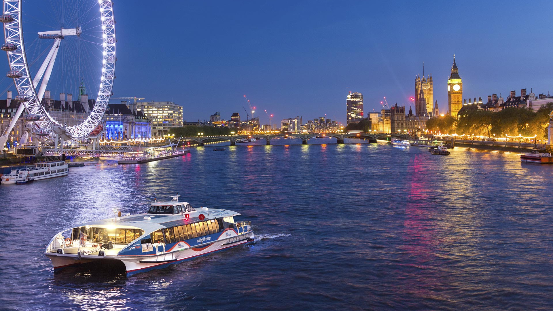 MBNA Thames Clippers boat on the Thames in the evening