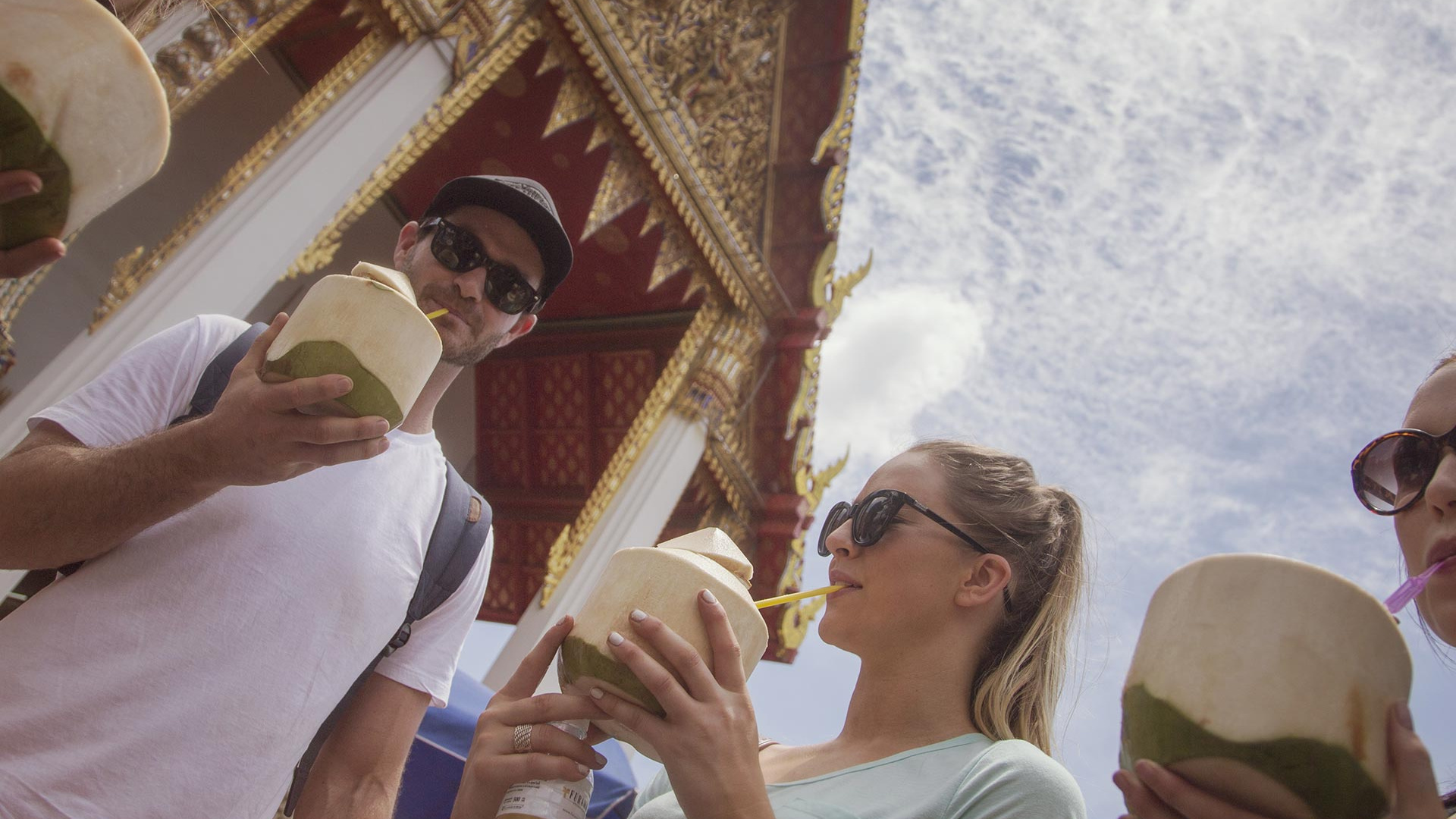 Travellers drinking coconut water in Thailand