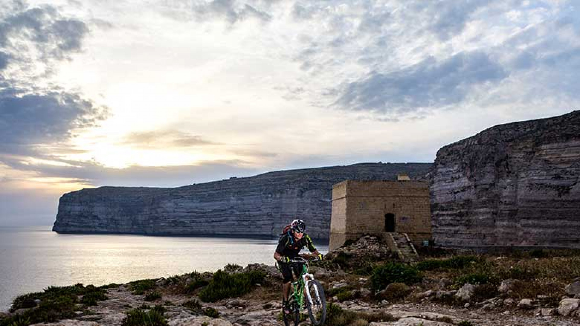Biking-by-Xlendi-Tower,-Xlendi