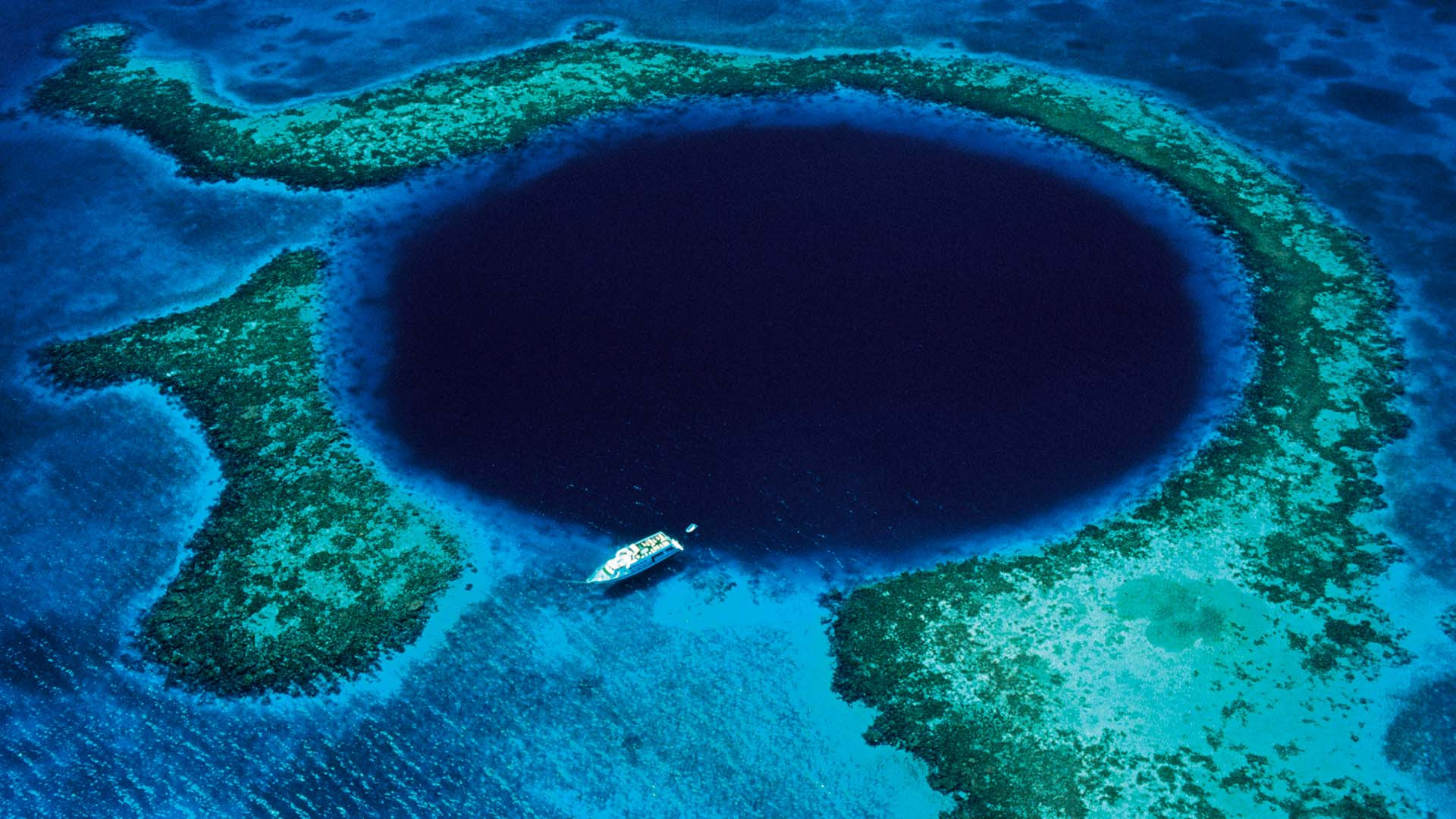 A boat passing over the Great Blue Hole of Belize