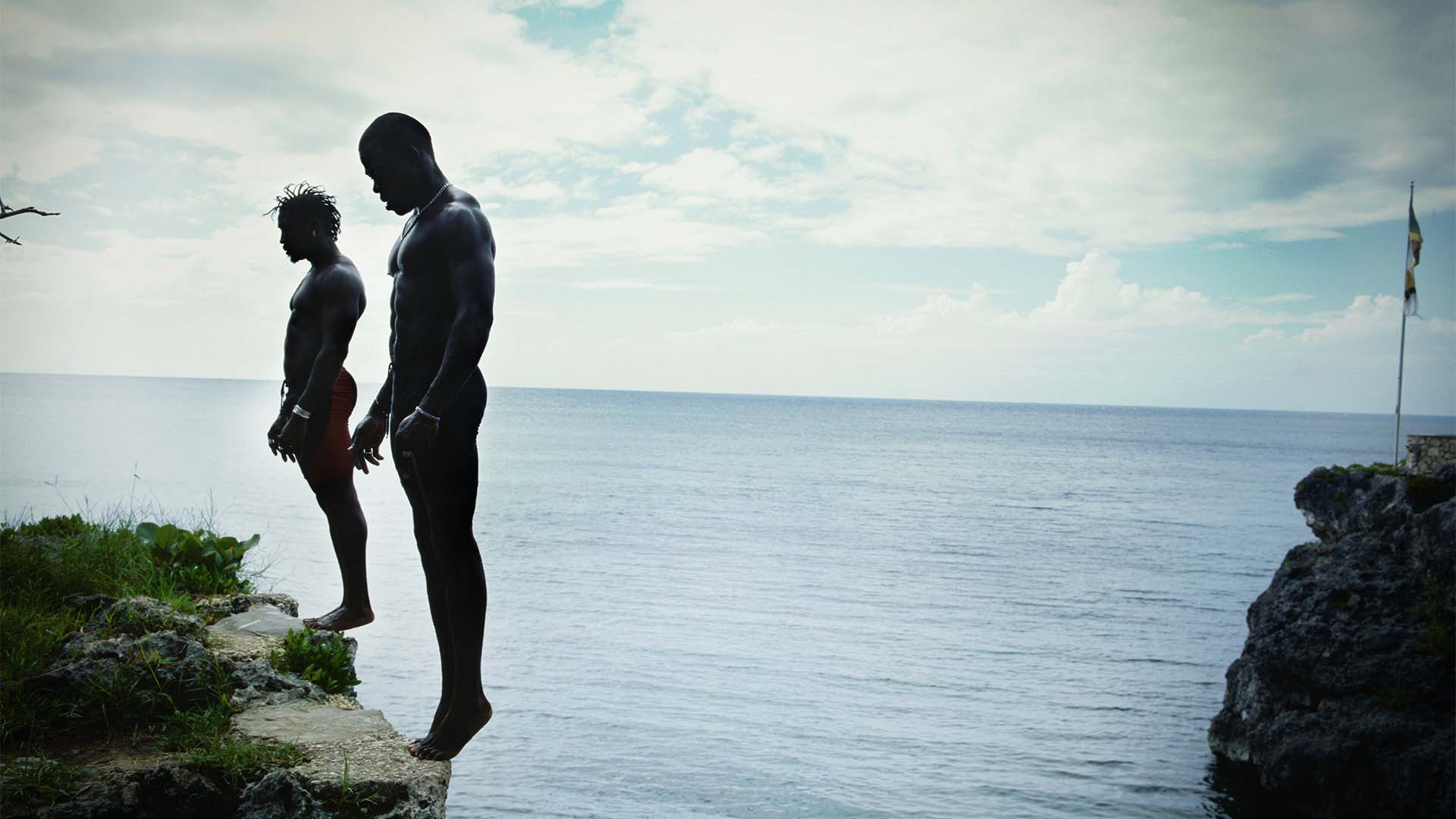 Two men prepare to dive from a cliff in Negril, Jamaica