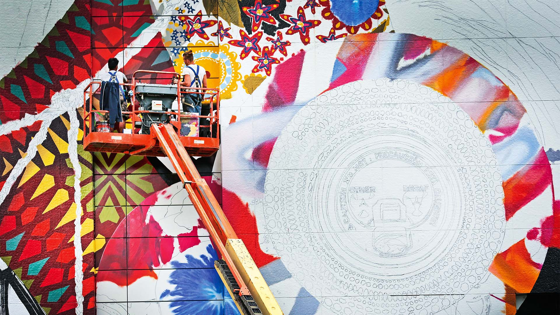 Two artists paint the Rose Kennedy Greenway mural from a cherry picker