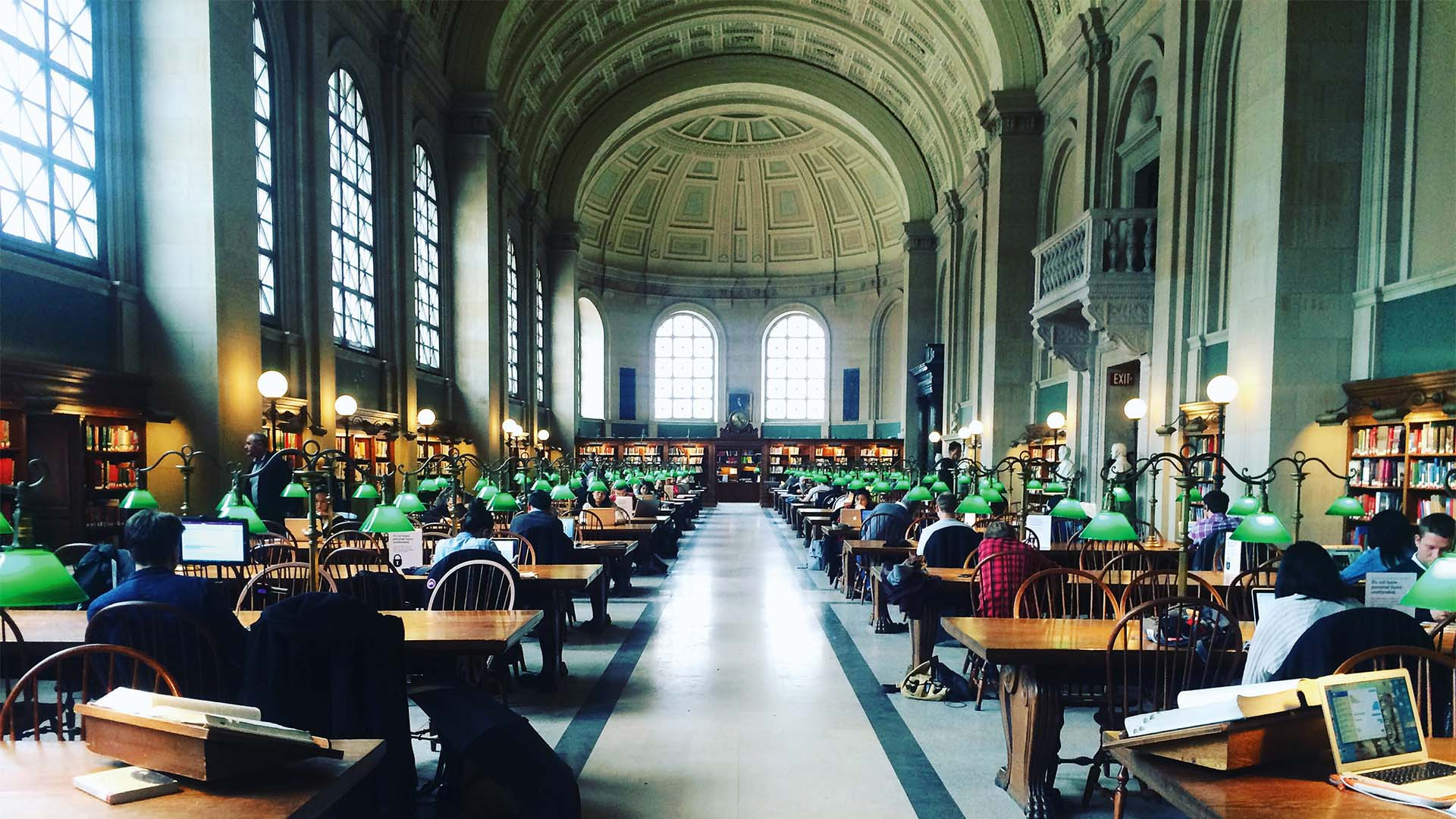 The inside of Boston Public Library, with lamps lit and people at work