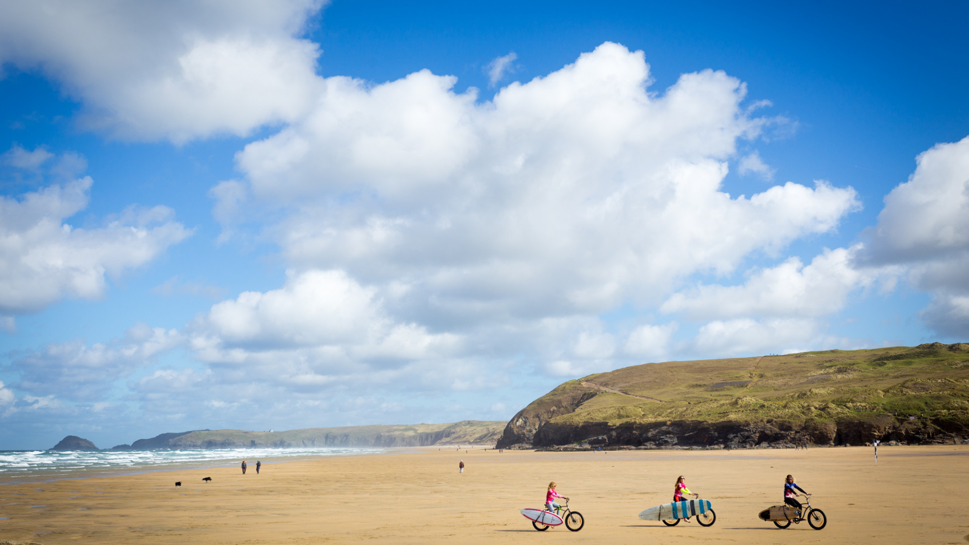 A family cycle the beach in Cornwall