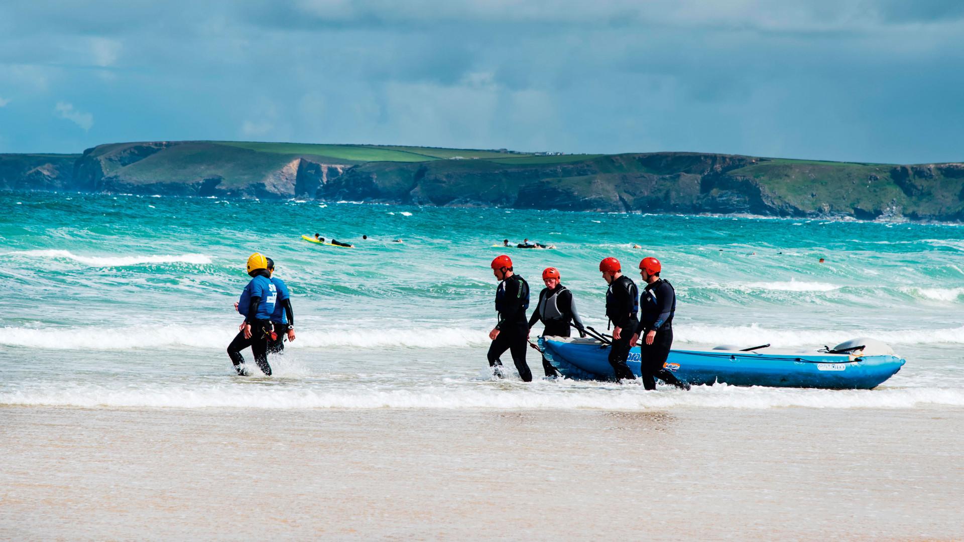 A group walk their raft into the Cornish sea