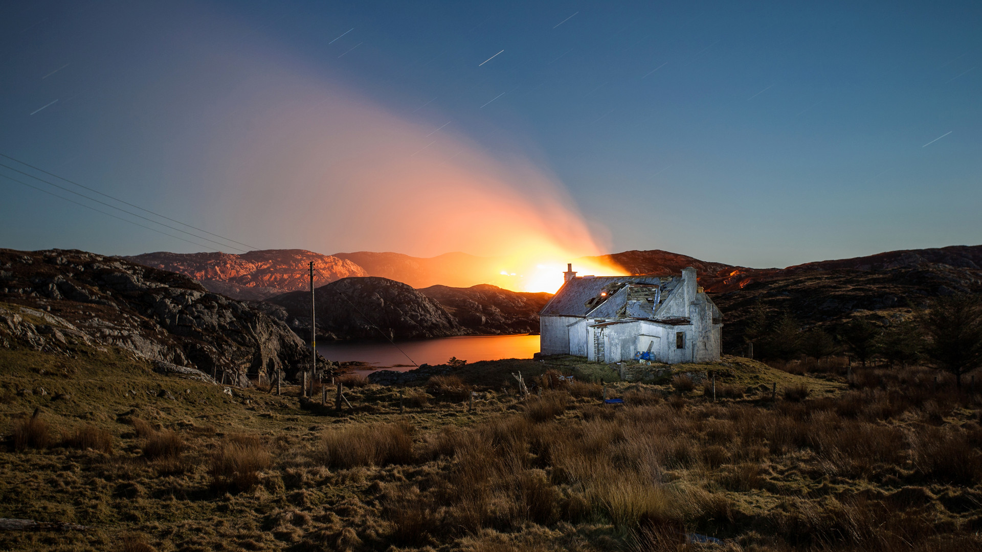 Fire behind a dilapidated croft on Harris