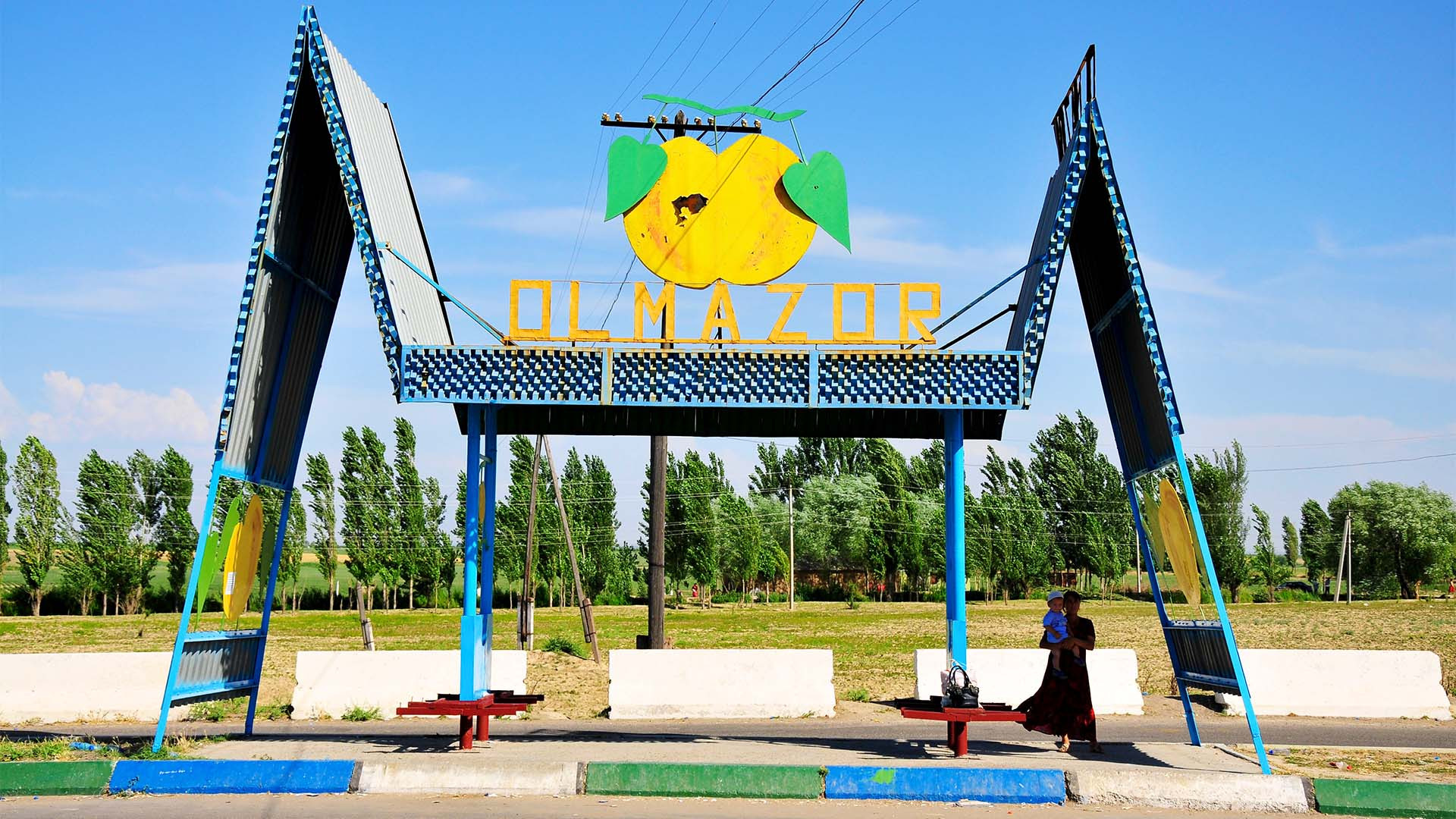Dual triangle bus stop in Uzbekistan with lemon advertisment
