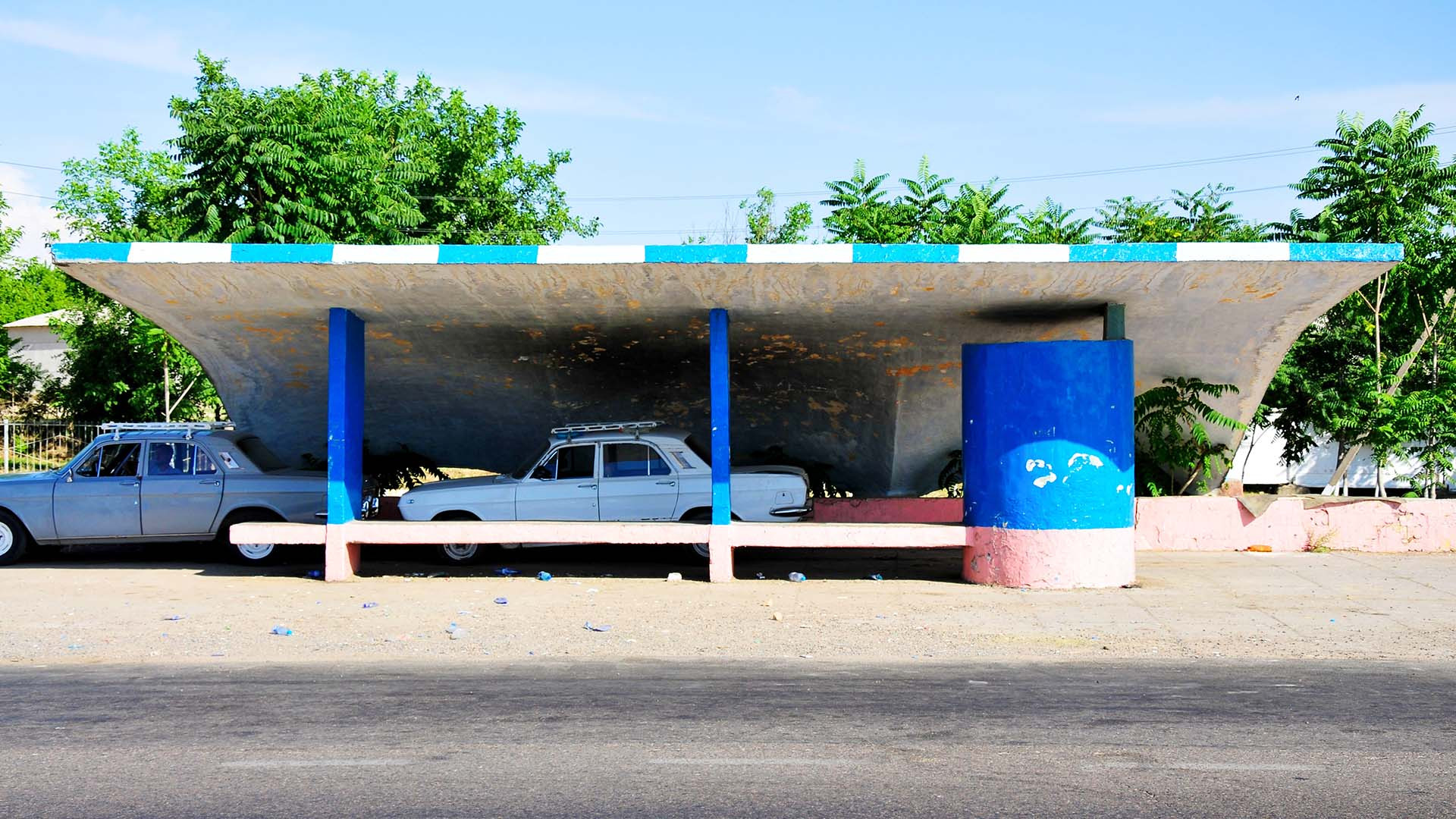 A bus stop with two cars underneath