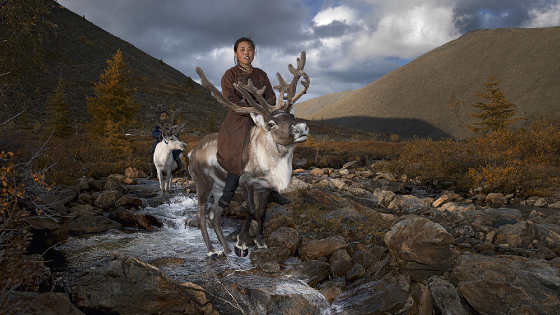 A mother and child ride reindeer on the Mongolian steppe