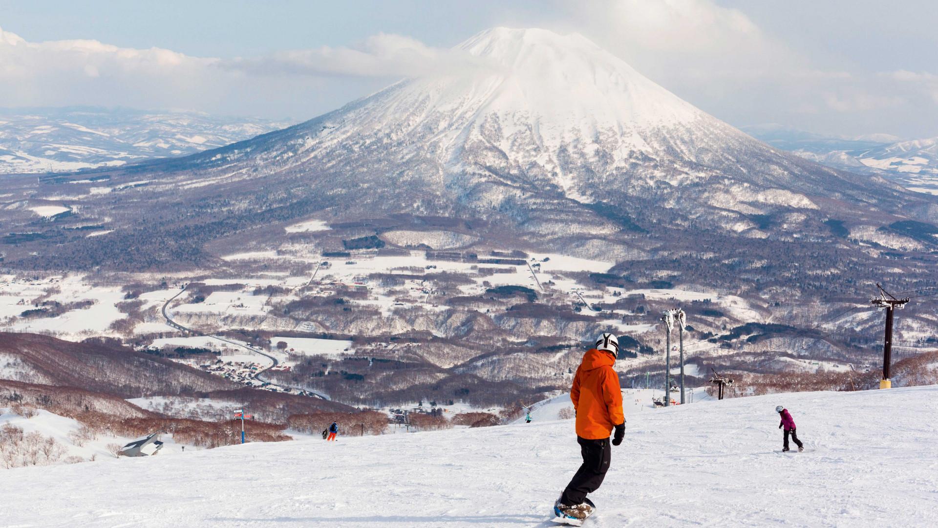 Snowboarder on slopes in Niseko, Japan, overlooking mountains