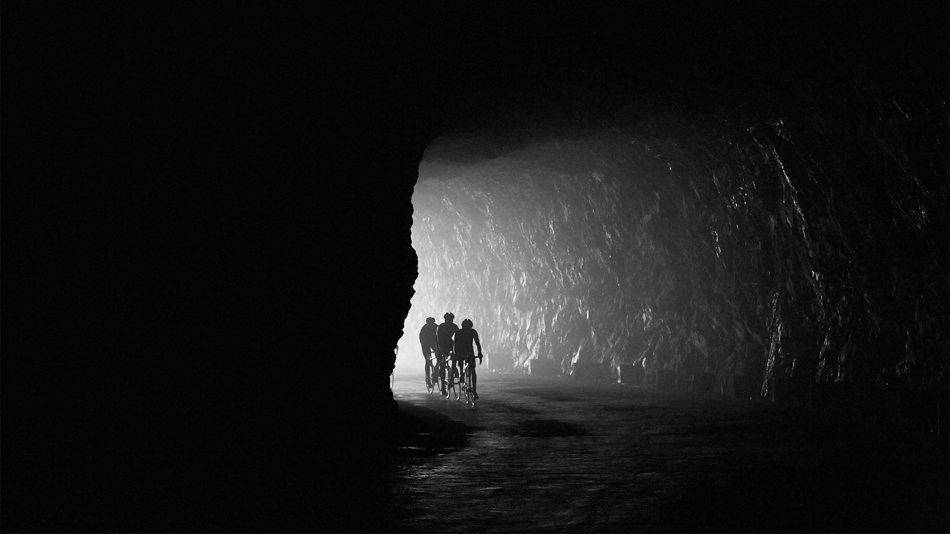 Cyclists coming into a tunnel in black and white in France