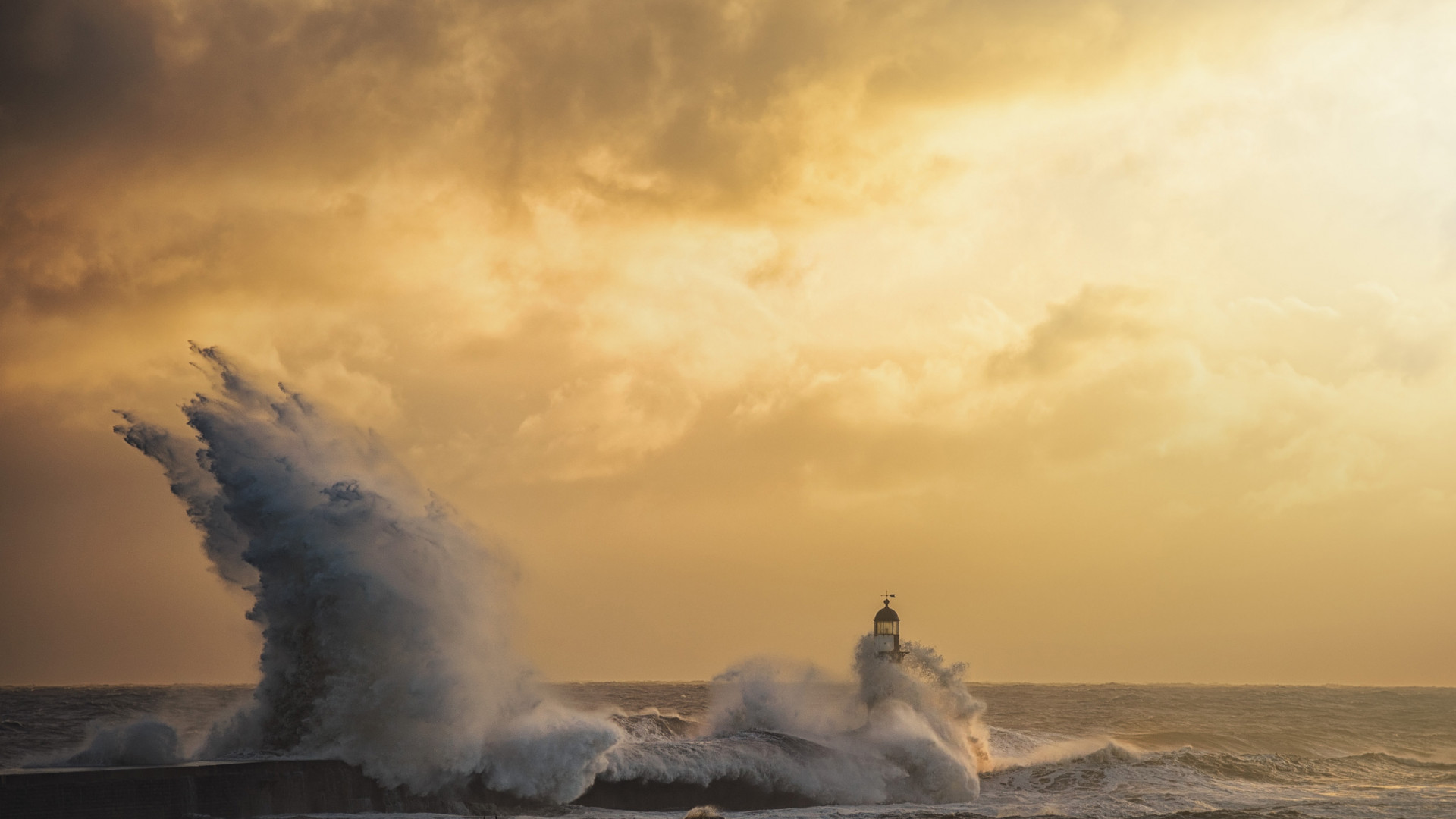 Huge waves hit the pier wall and lighthouse at Seaham Harbour, Durham