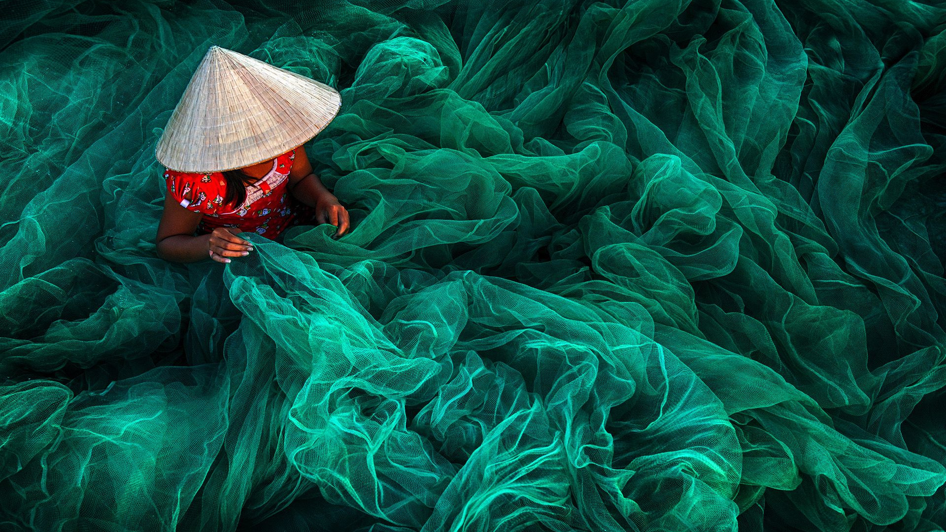 Vietnamese woman weaving a handmade fishing net