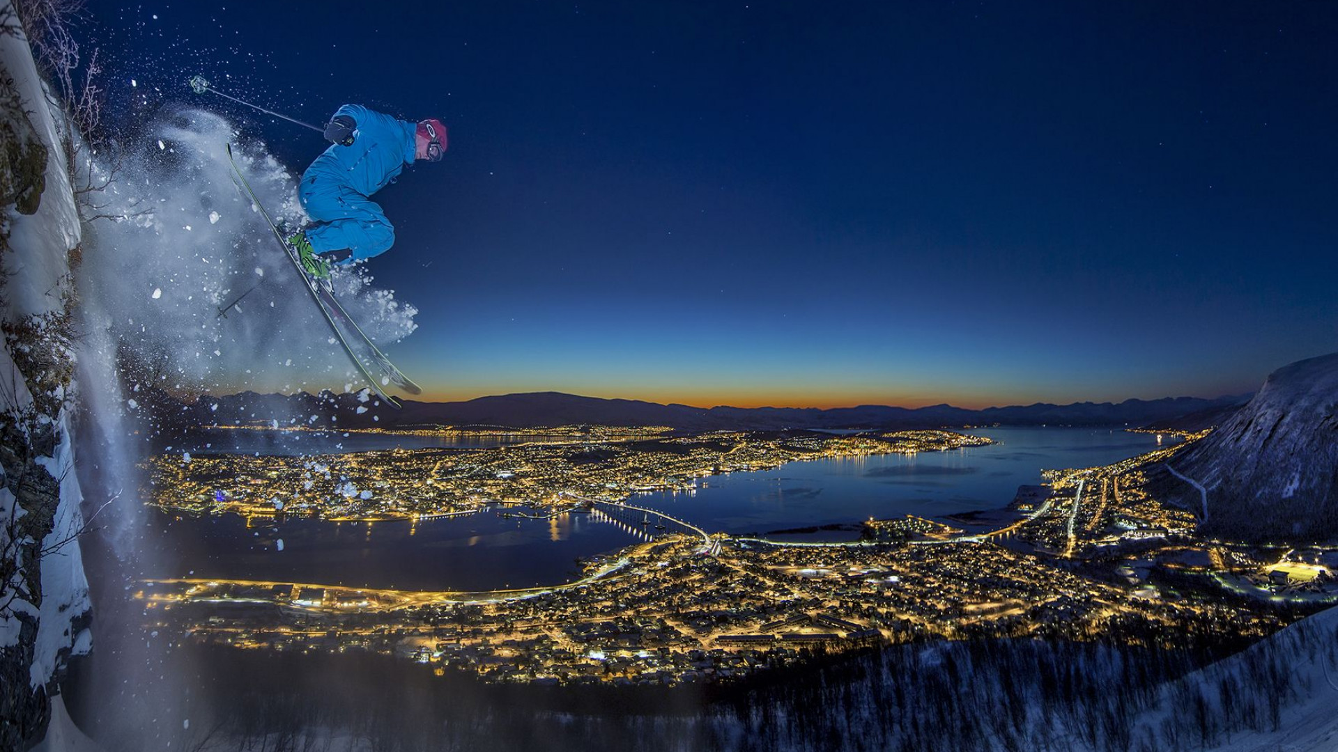 Skiier jumping off a clifftop in Tromso, Norway