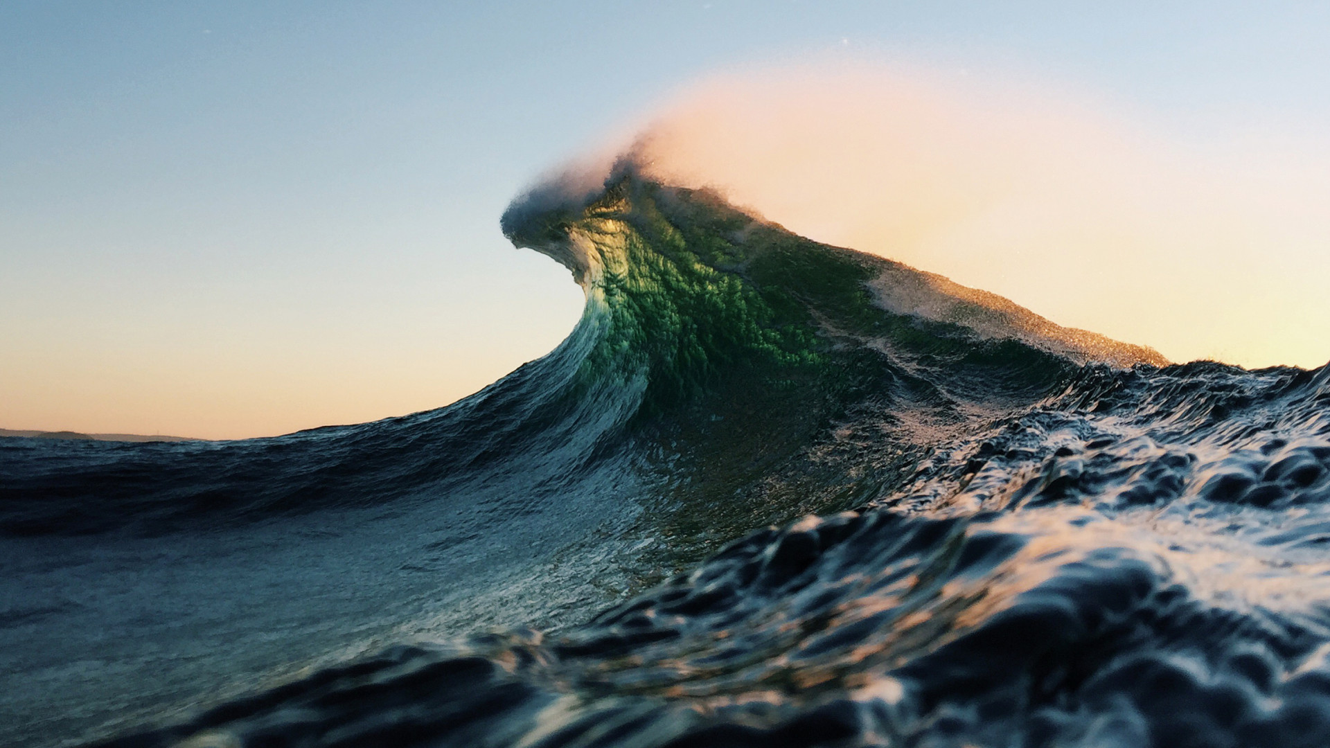 Light glowing through the top of an incoming wave