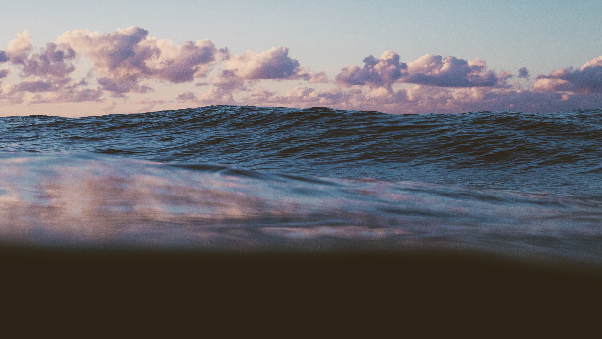 A rising wave with clouds reflected in the water