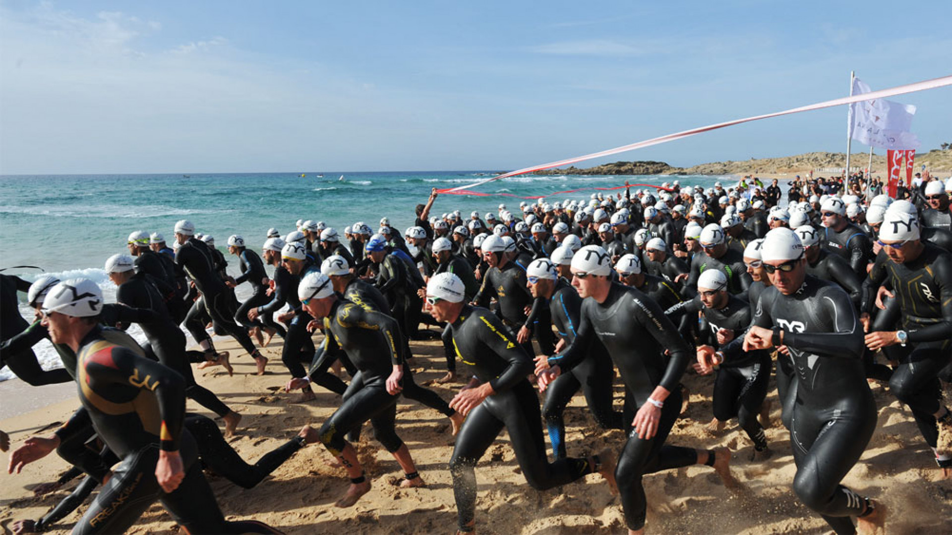 Swimmers enter the sea at the Chia Sardinia Triathlon