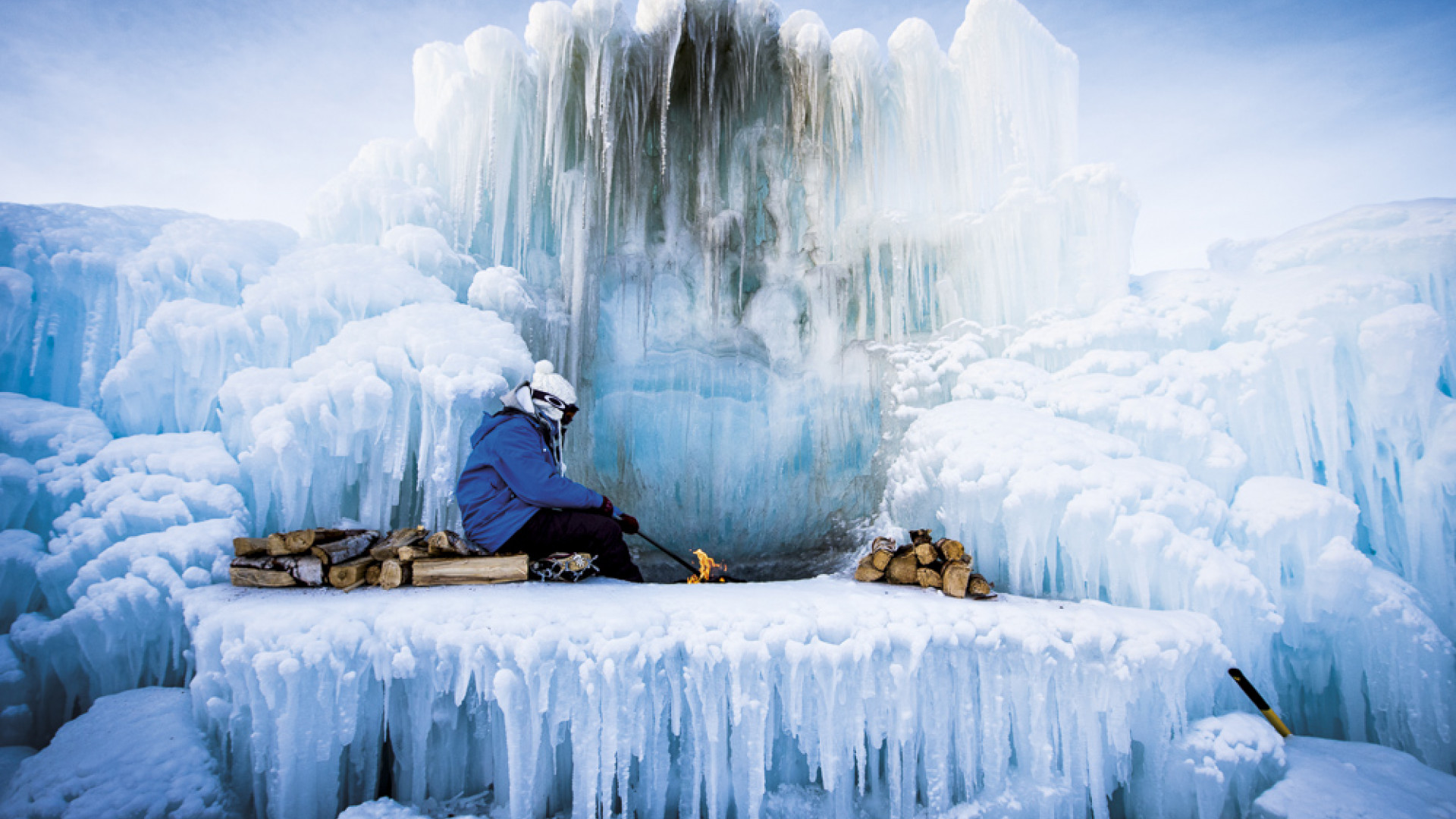 A woman sitting surrounded by ice in a frozen fire pit