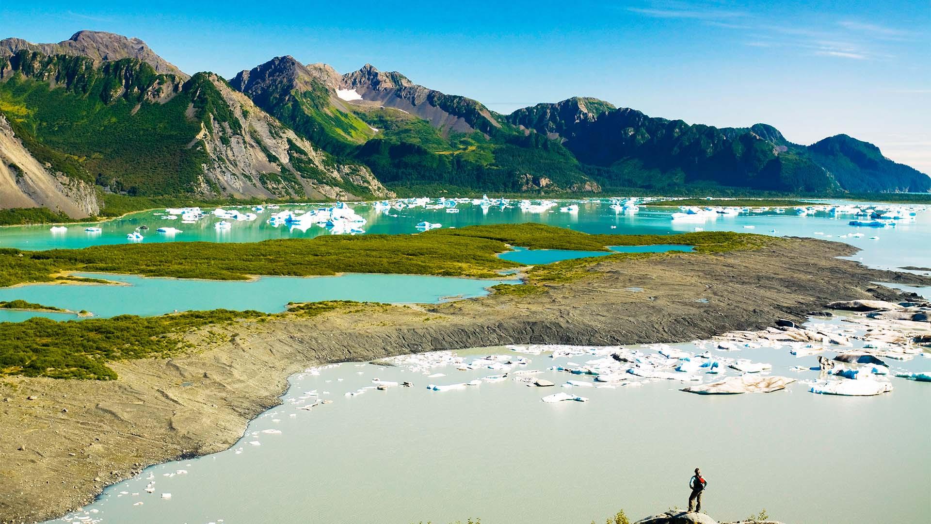 Female hiker overlooks Bear Glacier Lake in Kenai Fjords National Park, Kenai Peninsula, Southcentral Alaska, Summer