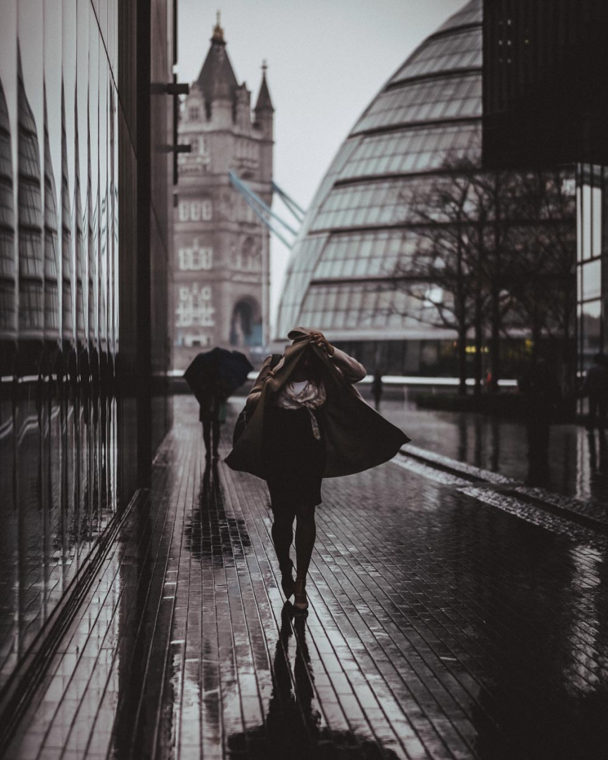 Woman sheltering under her coat in the City of London