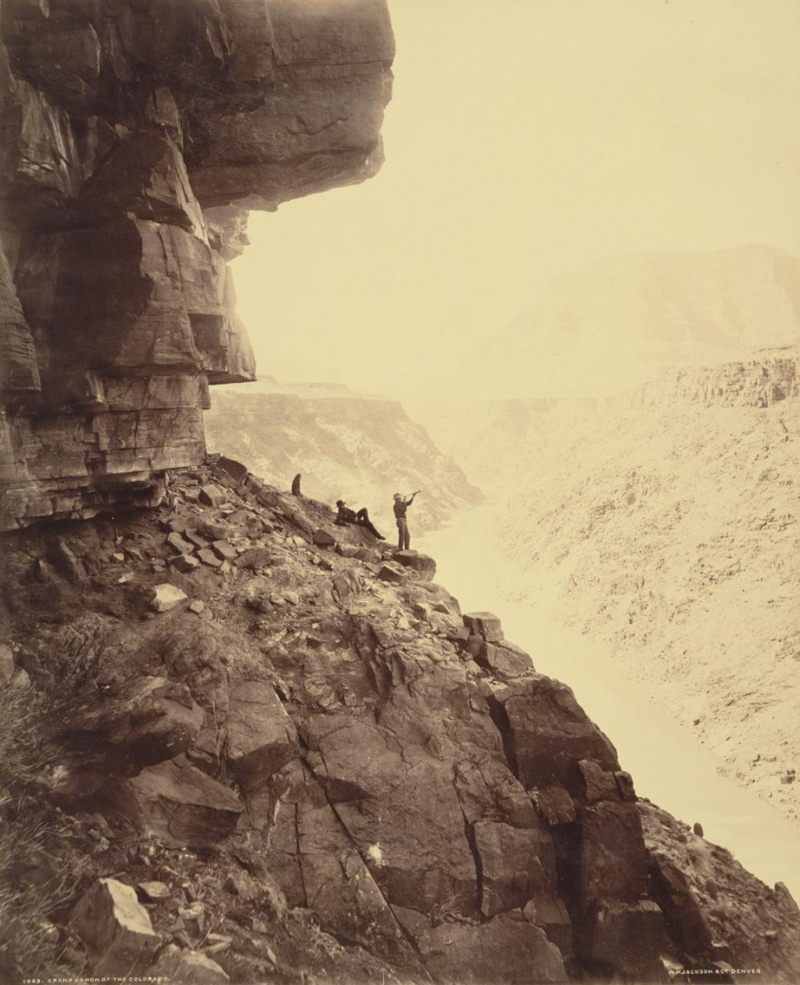 Two men stand next to the Grand Canyon near the Colorado River
