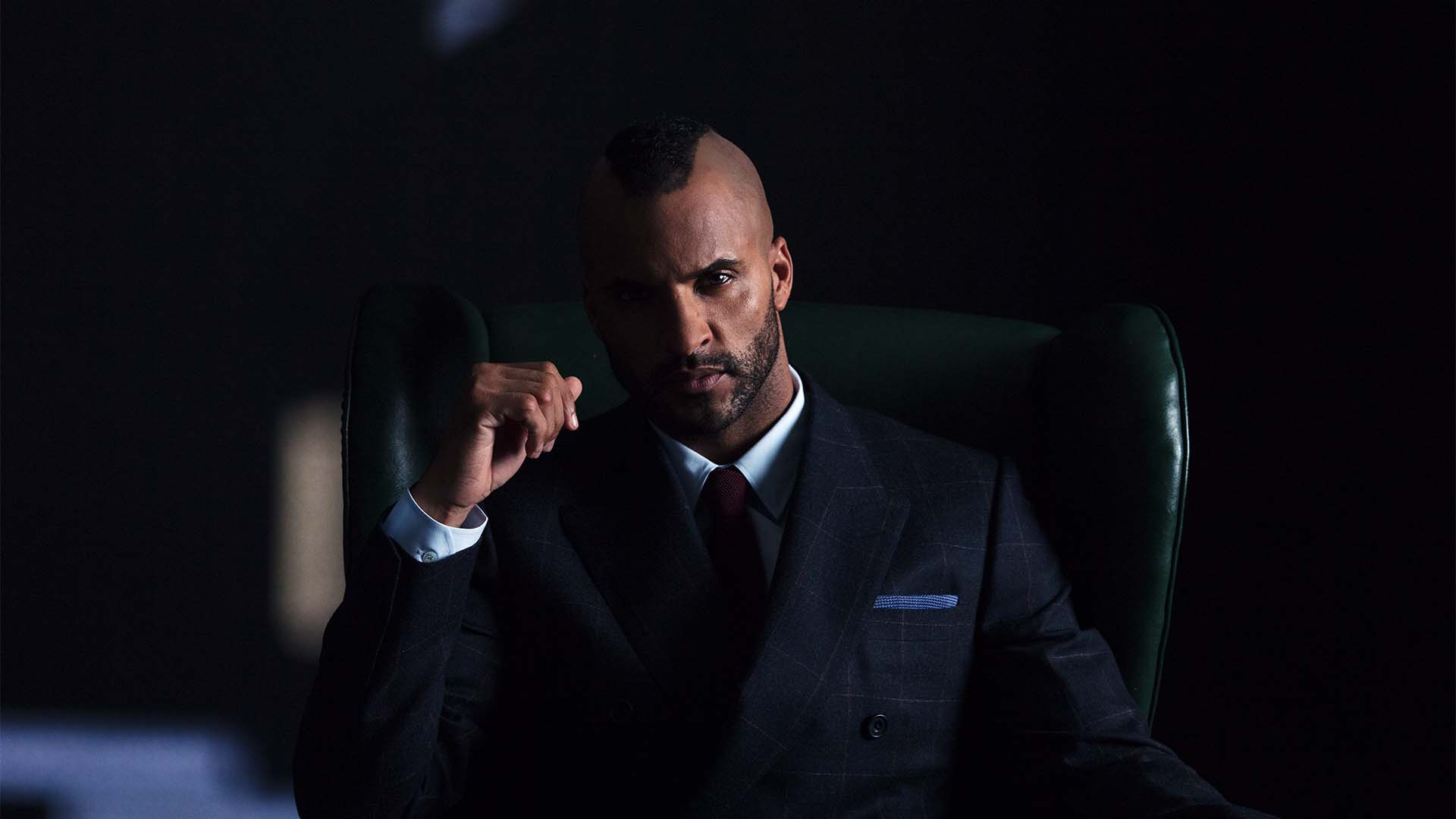 Ricky Whittle, star of American Gods poses in a suit and macintosh
