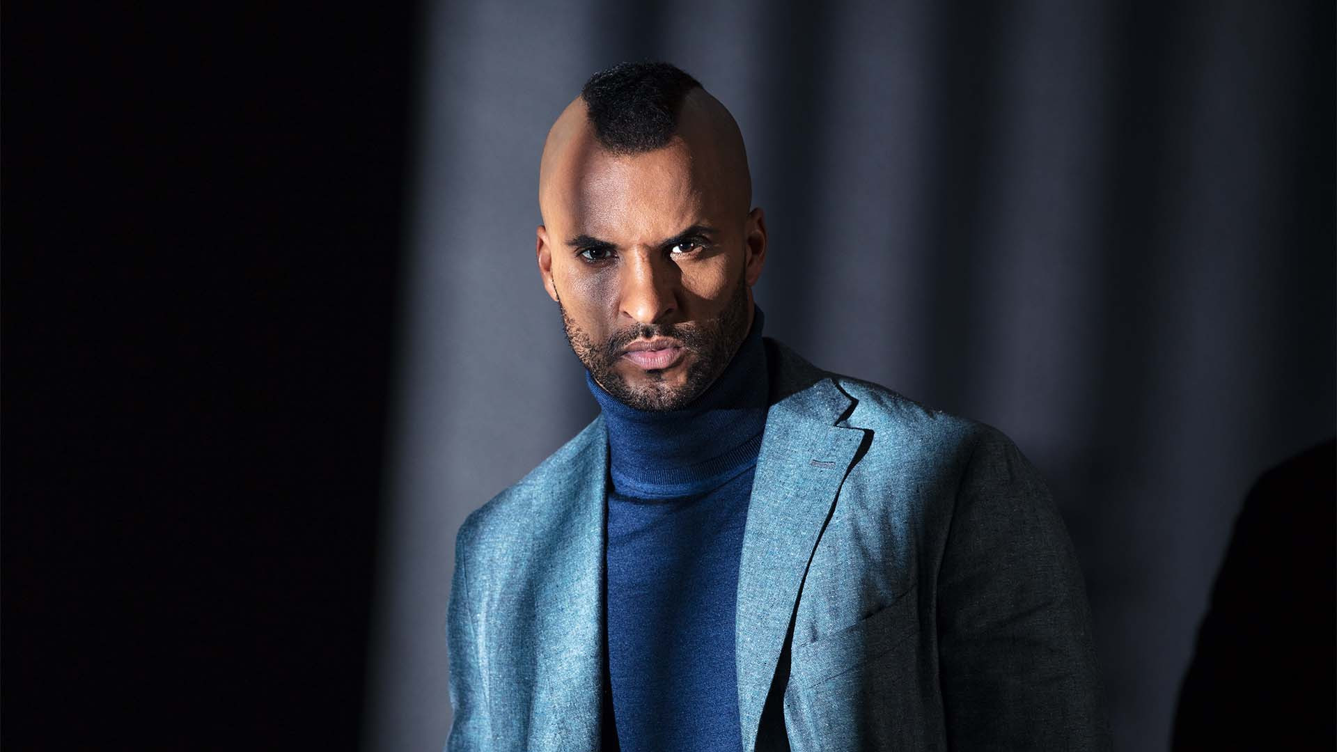 Ricky Whittle, star of American Gods on Amazon Prime, poses in a roll neck