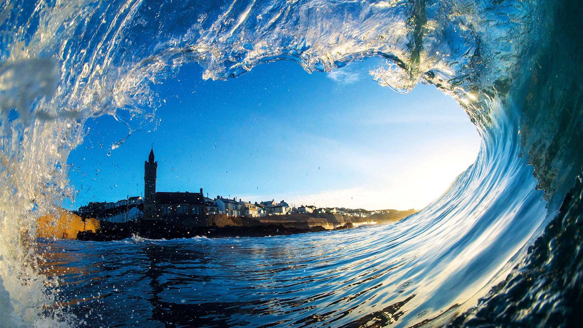 A wave in Porthleven framing the Cornish town's skyline