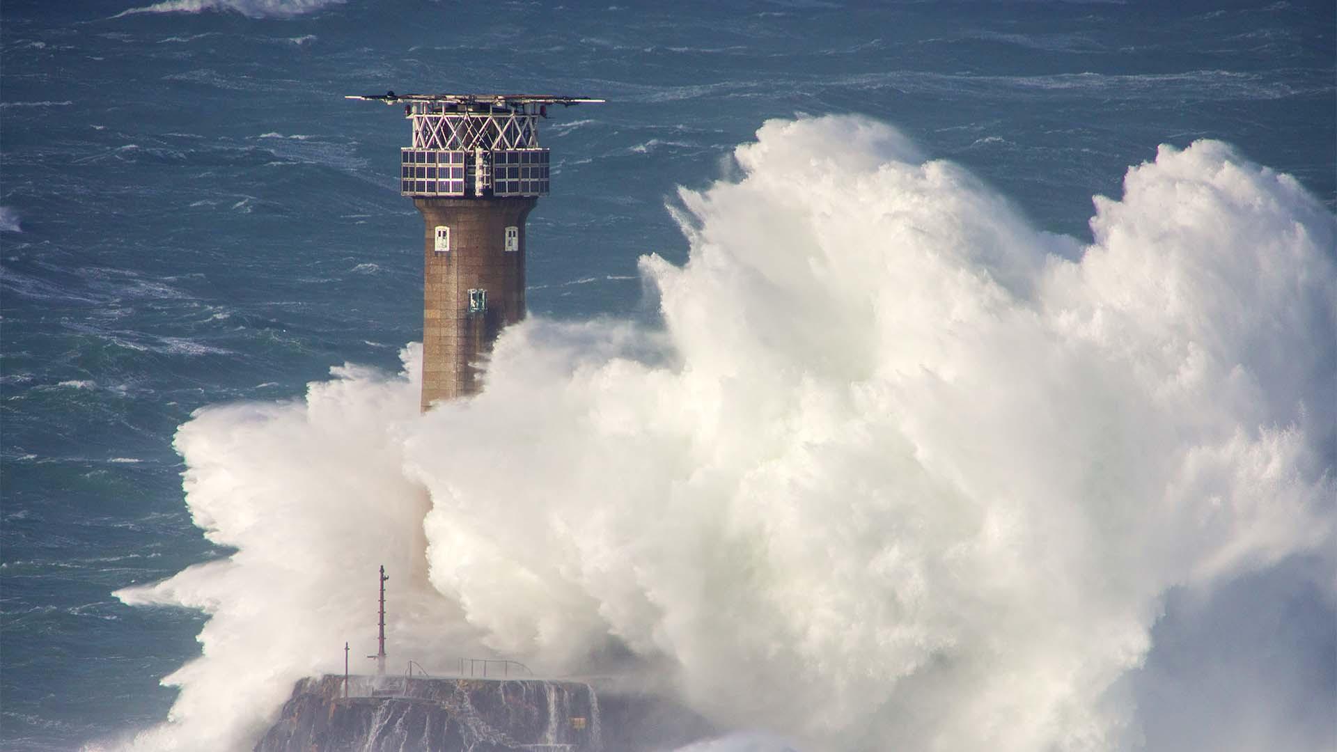 Waves breaking on Longships watch in Sennen Cove, Cornwall