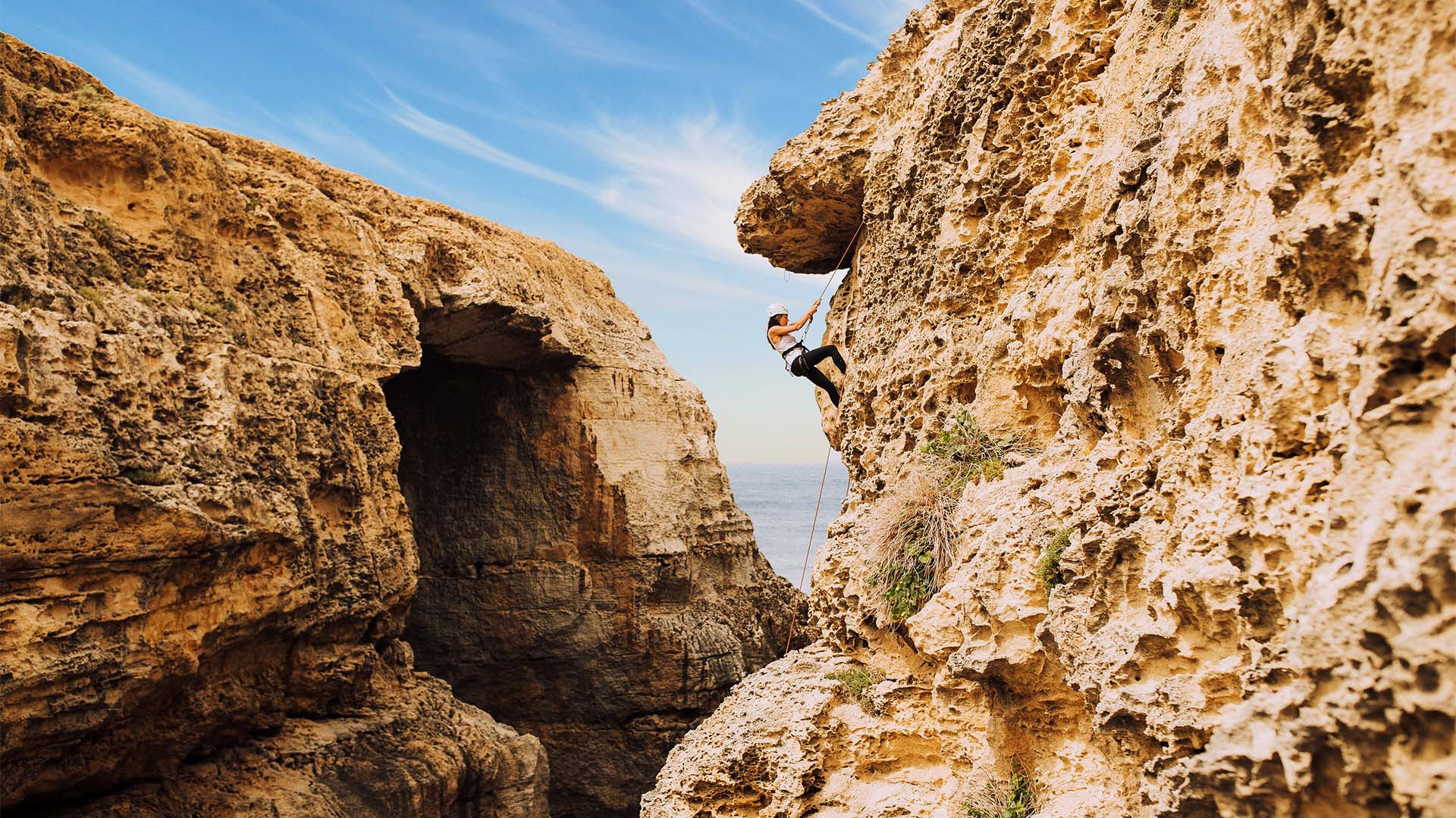 A young woman climbing the cliffs of Gozo, Malta