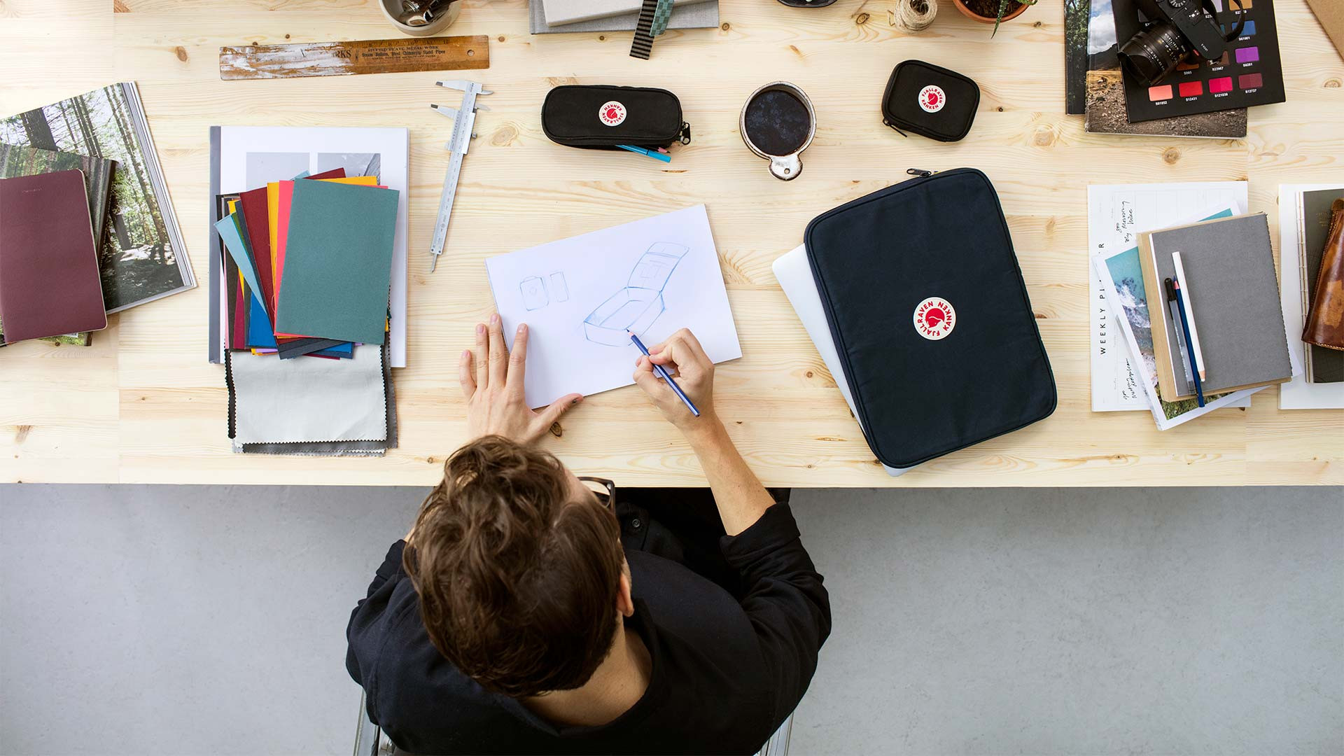 A designer working at a desk with the Fjallraven Kanken Essentials kit