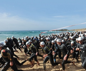 Swimmers enter the water in the first leg of the Chia Laguna Triathlon