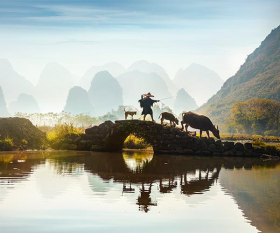 Farmer on bridge in Yangshuo, China