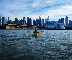 Hannah Summers kayaks with the New York skyline in the background