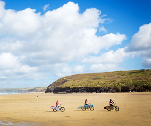 Family cycle on the beach holiday Cornwall