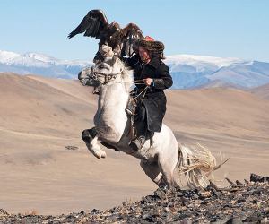 A mongolian hunter on horseback with an eagle