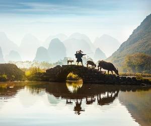 Farmer on bridge in Yangshuo, China