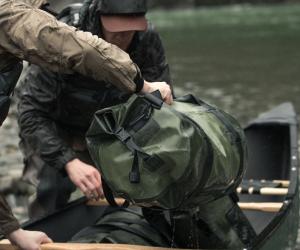 Loading a Filson dry duffel bag into a canoe